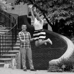 Laura jumps from a low wall while Aaron looks on