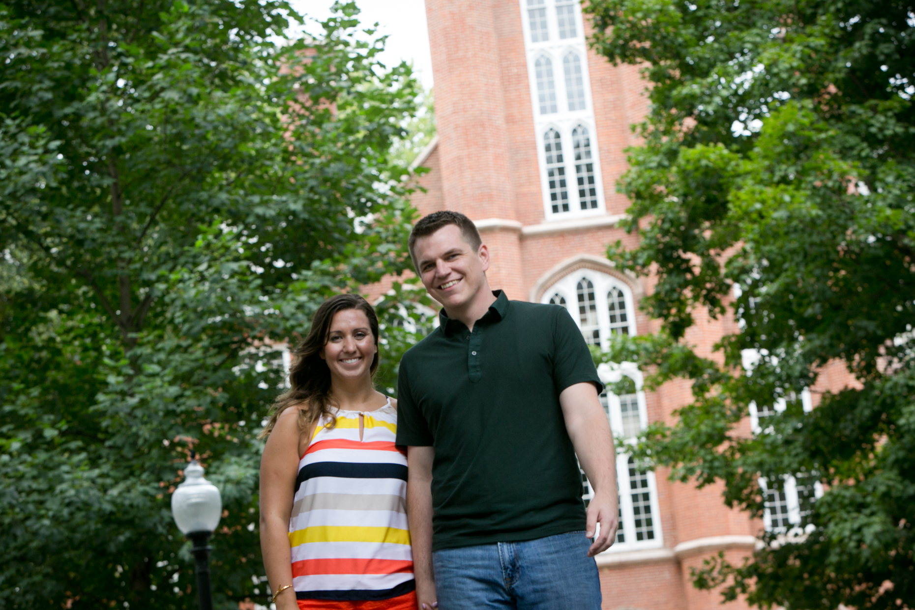 Laura and Aaron hold hands in front of a brick cathedral